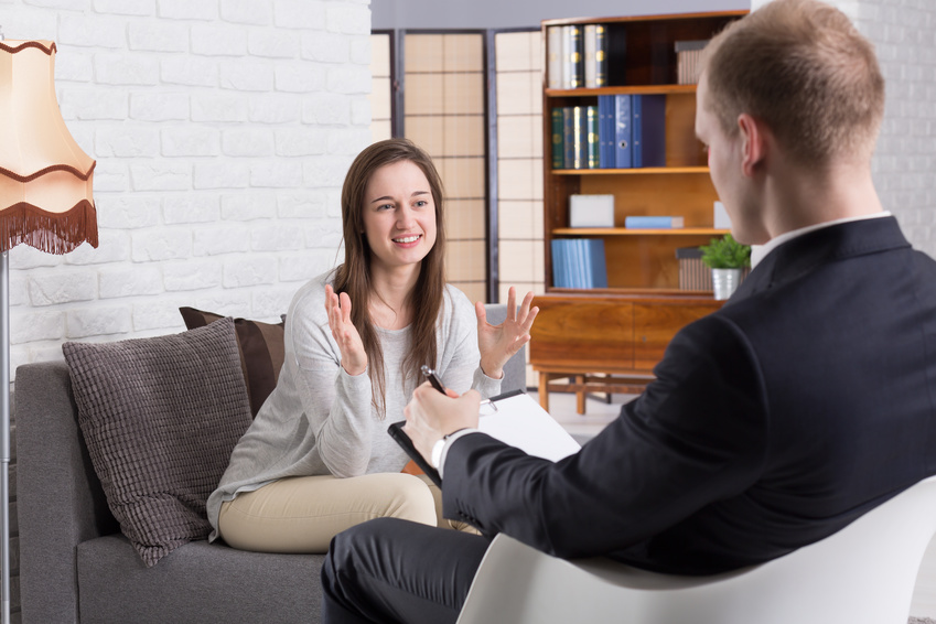 Young pretty girl talking excitedly about her life to young elegant psychotherapist at man's cabinet. Man making notes